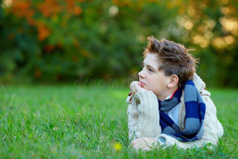 Stående av den tonårs- pojken som är grön utomhus arkivbild