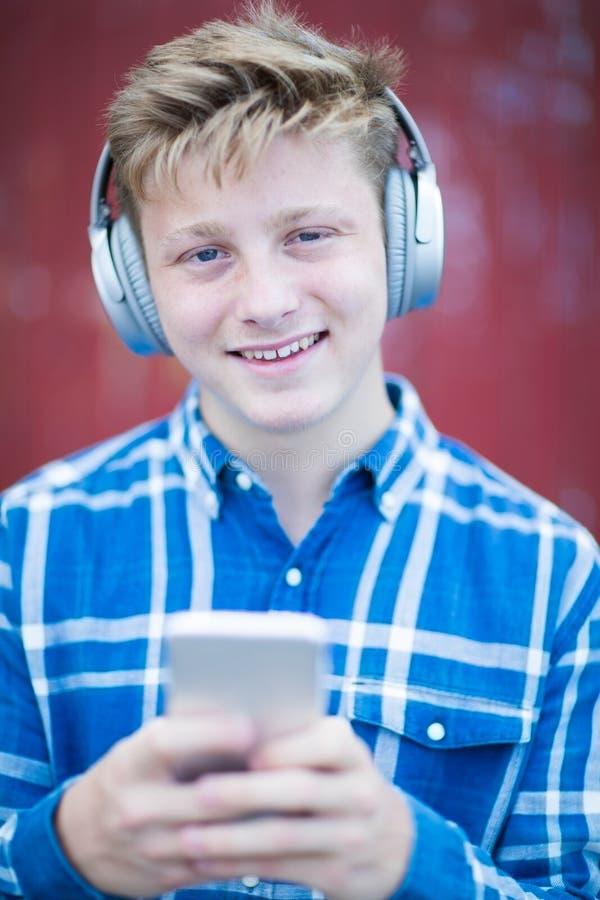 Stående av den tonårs- pojken som bär trådlös hörlurar och lyssnar till musik i stads- inställning royaltyfria bilder