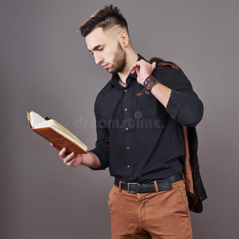 Stående av den toothy stiliga skäggiga mannen med boken på händer arkivbilder