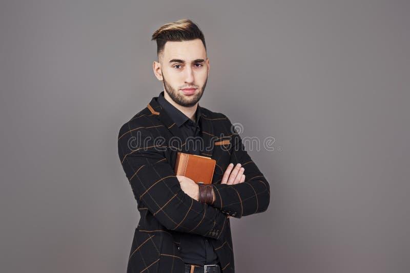 Stående av den toothy stiliga skäggiga mannen med boken på händer royaltyfri foto