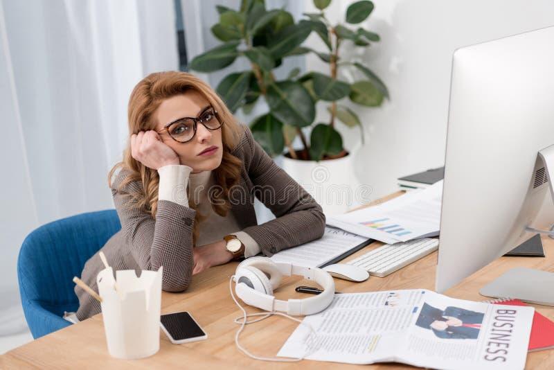stående av den trötta affärskvinnan i glasögon som sitter på arbetsplatsen arkivfoton