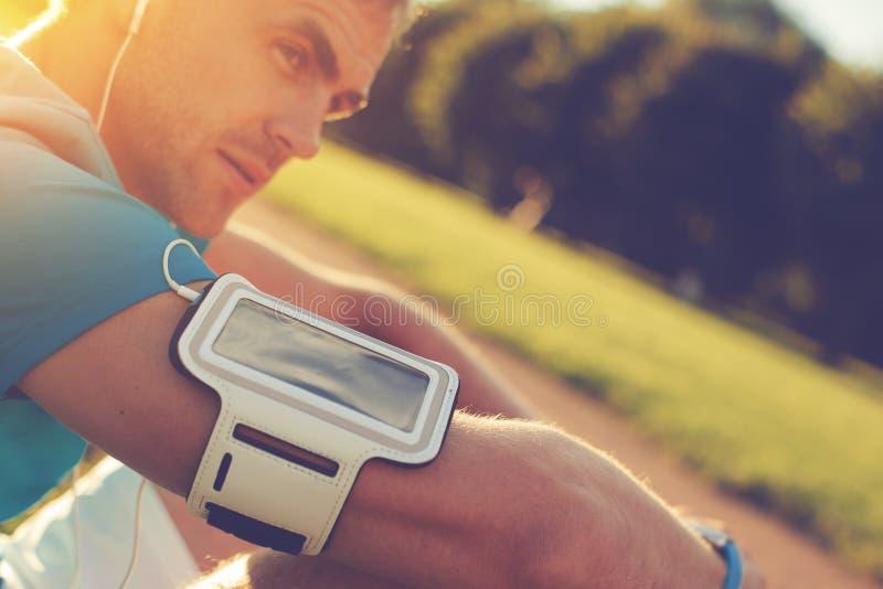 Stående av den trötta idrottsman nen med armbindeln som vilar i parkera royaltyfri foto