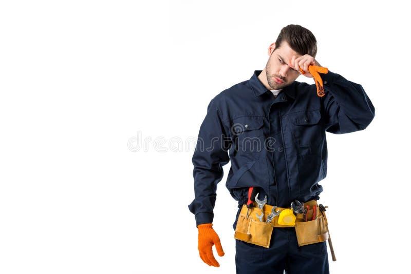 stående av den trötta rörmokaren i enhetliga och skyddande handskar som bort ser royaltyfri bild