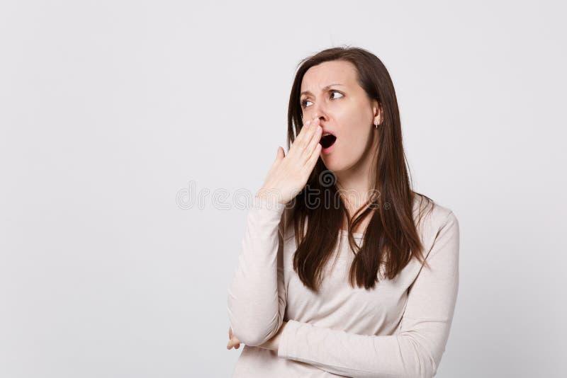Stående av den trötta tråkiga unga kvinnan i ljus kläder som åt sidan som ser gäspar den täckande munnen med handen på vit royaltyfri foto