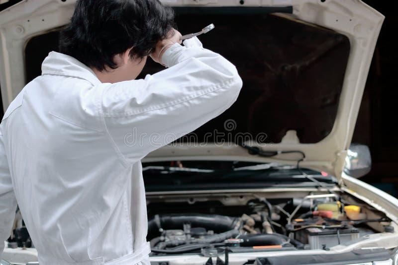 Stående av den trötta unga asiatiska mekanikermannen i likformig med skiftnyckeln med bilen i öppen huv på reparationsgaragebakgr arkivfoton