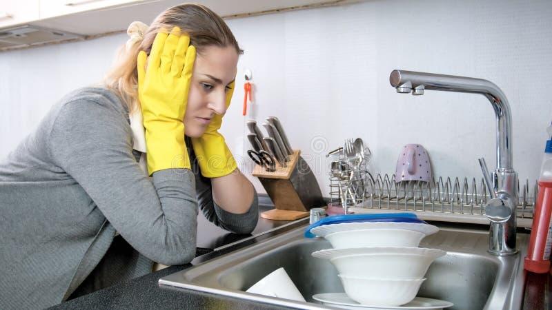 Stående av den trötta unga kvinnan som ser högen av smutsig disk royaltyfri foto