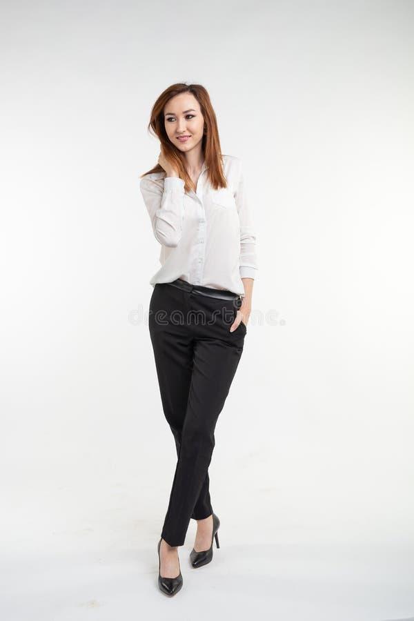 Stående av den trendiga härliga asiatiska kvinnan i elegant kläder över vit bakgrund royaltyfri fotografi