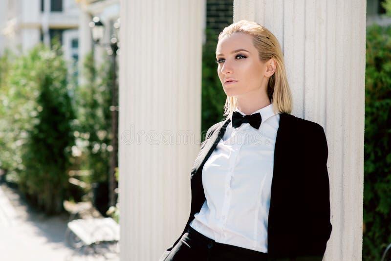 Stående av den trendiga härliga blonda kvinnan i mansvartdräkt med flugan arkivfoton