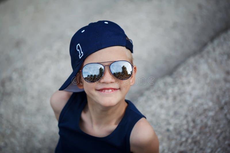 Stående av den trendiga pysen i solglasögon och lock Barndom royaltyfri fotografi