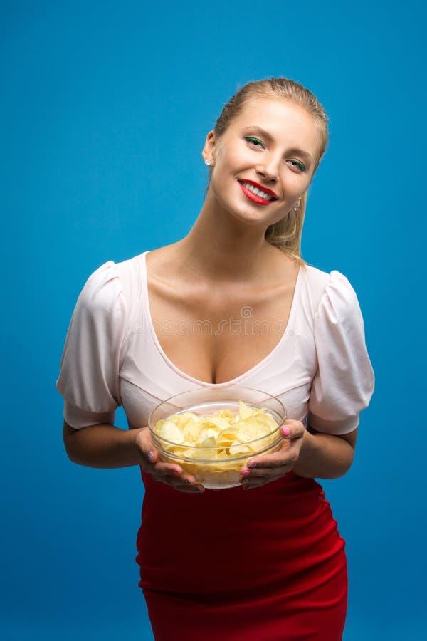 Stående av den trendiga unga blonda kvinnan i denröda klänningen, ljust sminkinnehav som äter den stekte potatisen, chiper och öv arkivbild