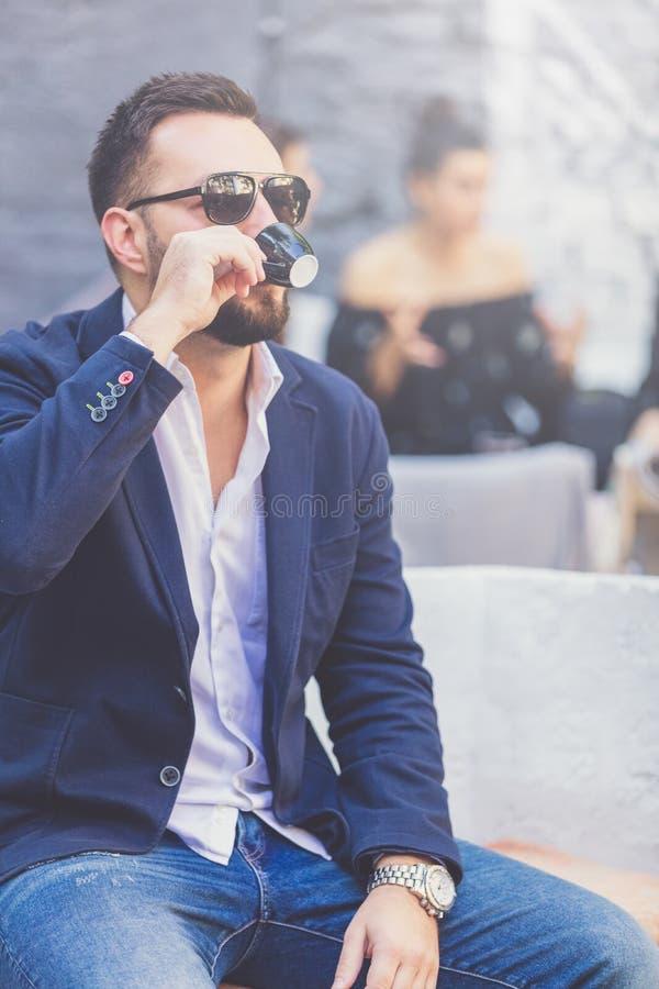 Stående av den trendiga unga mannen med koppen kaffe fotografering för bildbyråer
