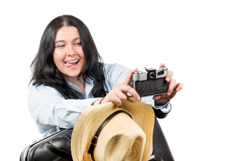 Stående av den turist- flickan för lycklig ung härlig brunett med hatten som gör selfie med den retro kameran och rymmer resväska arkivfoton