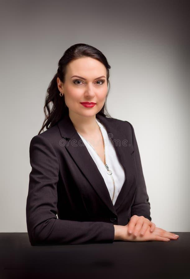 Stående av den underbara affärskvinnan på grå bakgrund arkivbild