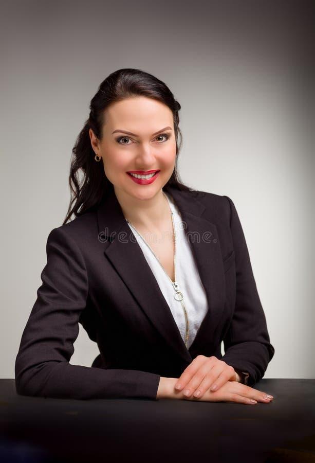 Stående av den underbara affärskvinnan på grå bakgrund fotografering för bildbyråer