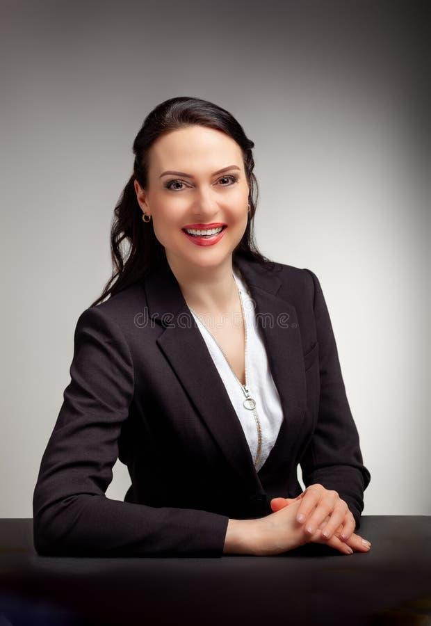 Stående av den underbara affärskvinnan på grå bakgrund arkivfoto