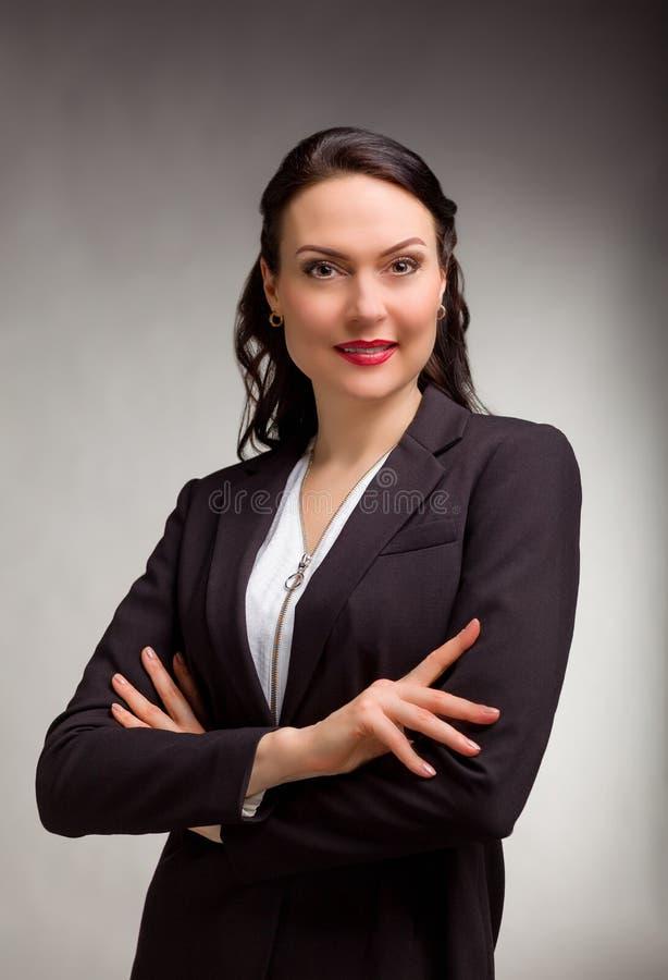 Stående av den underbara affärskvinnan på grå bakgrund royaltyfri bild
