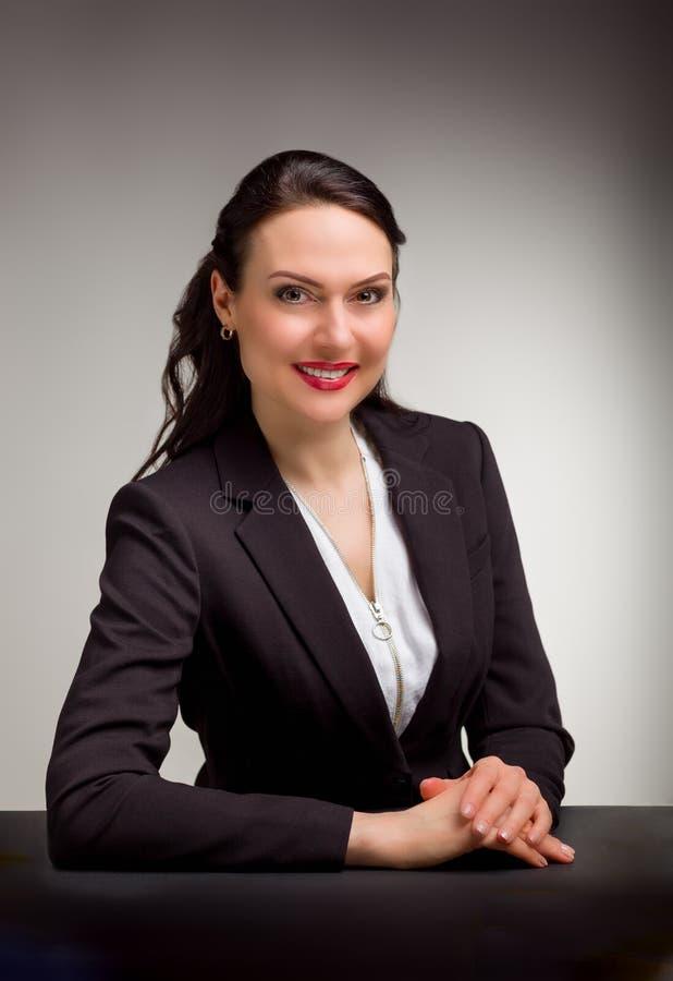 Stående av den underbara affärskvinnan på grå bakgrund royaltyfria bilder
