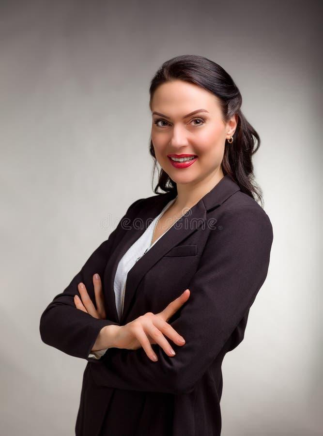 Stående av den underbara affärskvinnan på grå bakgrund arkivbilder
