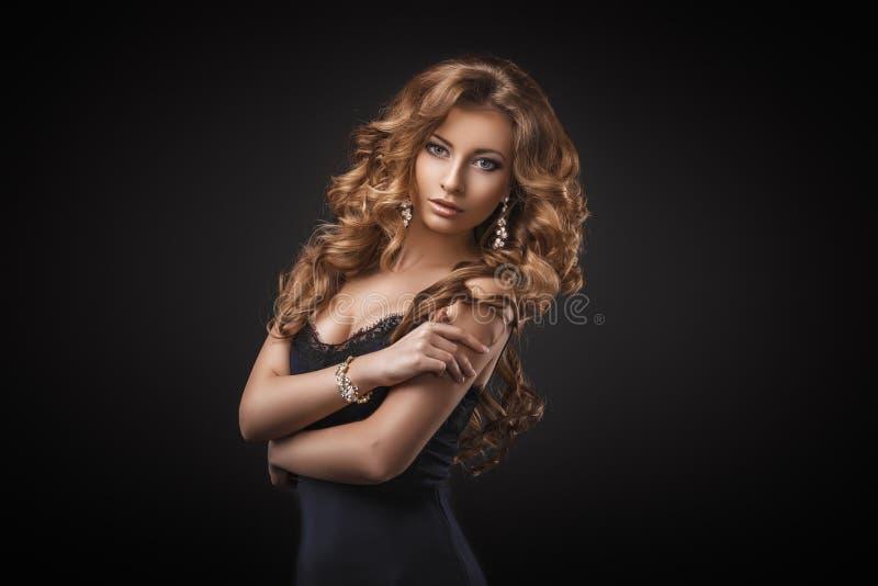 Stående av den underbara unga blonda kvinnan med långt hår som ser kameran blå mörk sexig klänningflicka arkivfoto