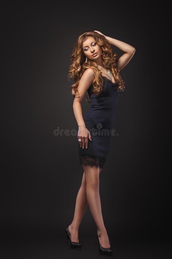 Stående av den underbara unga blonda kvinnan med långt hår som ser kameran blå mörk sexig klänningflicka fotografering för bildbyråer