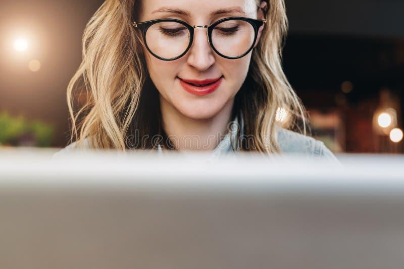 Stående av den unga affärskvinnan i moderiktiga exponeringsglas som sitter i kafé som arbetar på bärbara datorn Bloggeren meddela royaltyfria bilder