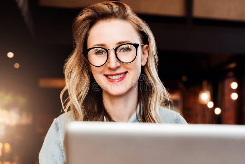 Stående av den unga affärskvinnan i moderiktiga exponeringsglas som sitter i kafé som arbetar på bärbara datorn Bloggeren meddela arkivfoton