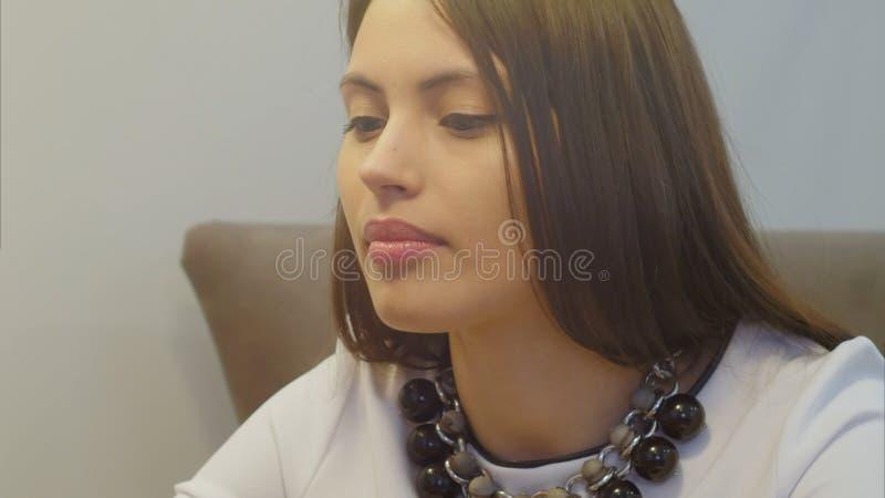 Stående av den unga affärskvinnan med härlig nacklace som sitter och talar till någon arkivbilder