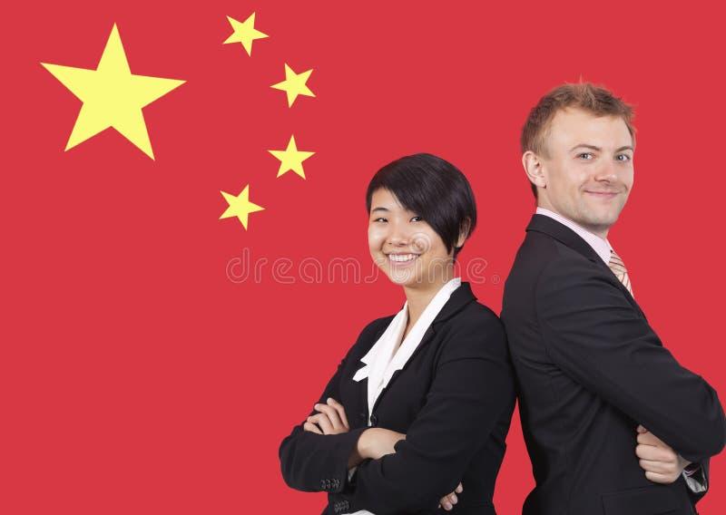 Stående av den unga affärskvinnan och mannen som ler över kinesisk flagga arkivfoton