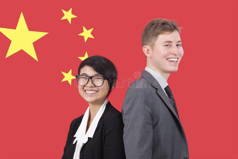 Stående av den unga affärskvinnan och mannen som ler över kinesisk flagga arkivbilder
