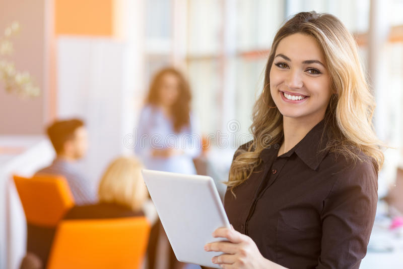 Stående av den unga affärskvinnan på den moderna startup kontorsinre, lag i möte i bakgrund arkivbilder