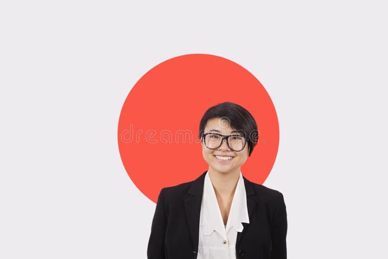 Stående av den unga affärskvinnan som ler över japansk flagga arkivfoto