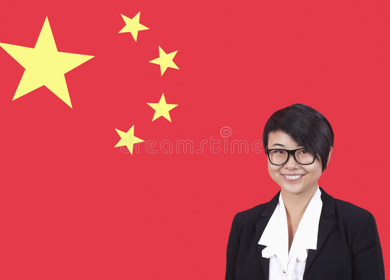 Stående av den unga affärskvinnan som ler över kinesisk flagga royaltyfri fotografi