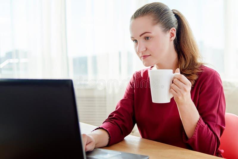 Stående av den unga affärskvinnan som sitter på träskrivbordet med koppen kaffe och skriver på bärbar datordatoren i modernt kont arkivbilder
