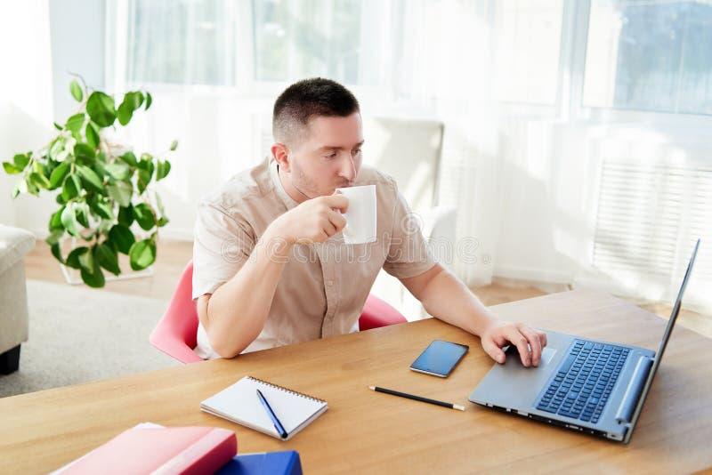 Stående av den unga affärsmannen som sitter på träskrivbordet, tycker om kaffe och arbetar på bärbar datordatoren i modernt konto royaltyfria bilder