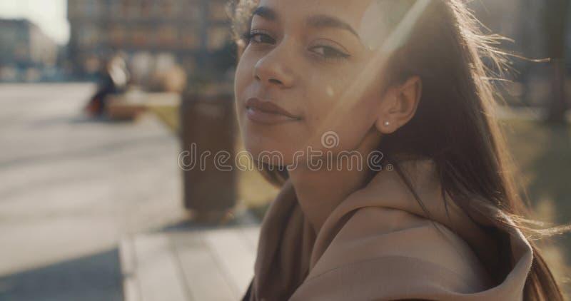 Stående av den unga afrikansk amerikankvinnan som ser till en kamera, utomhus långsam rörelse arkivbild