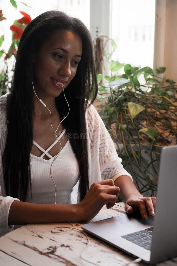 Stående av den unga afrikanska kvinnan som kopplar av i kafé med bärbara datorn och gör påringning, livsstil och folkbegrepp arkivbilder