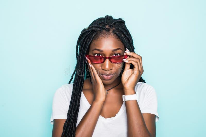 Stående av den unga afrikanska kvinnan som ler att se på kamera i modern solglasögon som isoleras över blå bakgrund royaltyfri foto