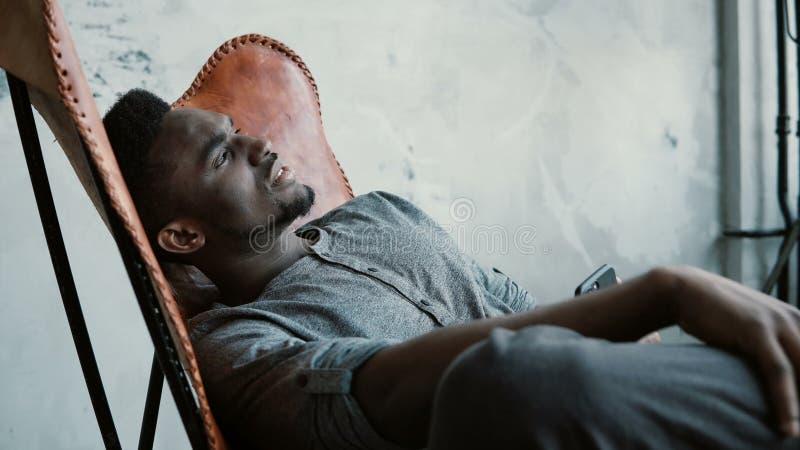 Stående av den unga afrikanska mannen i stol Mannen är allvarligt att tänka som rymmer Smartphone Grabbmaskinskrivningmeddelande  royaltyfri fotografi
