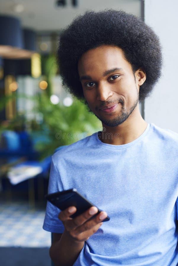 Stående av den unga afrikanska mannen som använder mobiltelefonen royaltyfri foto