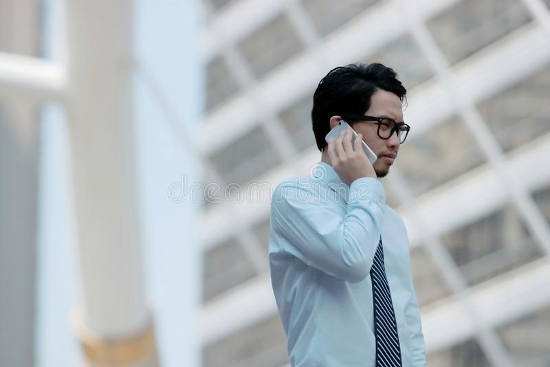 Stående av den unga asiatiska affärsmannen som talar på telefonen för hans jobb på utomhus- gatabakgrund arkivbilder