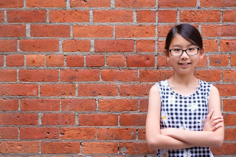 St?ende av den unga asiatiska flickan mot v?ggen f?r r?d tegelsten royaltyfria foton