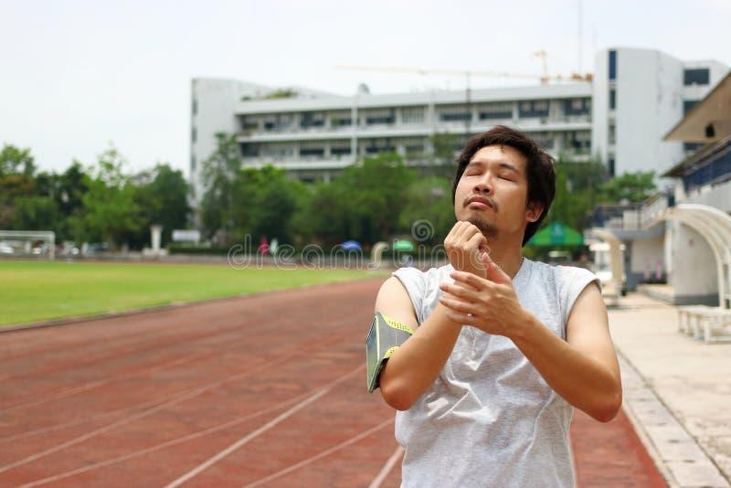 Stående av den unga asiatiska idrottsman nen som värmer upp och sträcker, innan att köra på ett rinnande spår royaltyfri foto