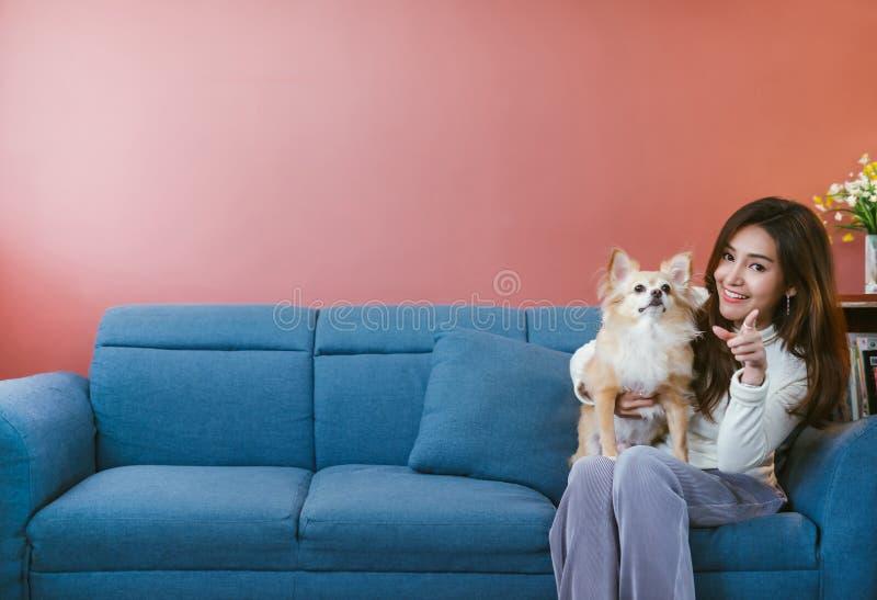 Stående av den unga asiatiska kvinnan som hemma rymmer hennes hundchihuahua på soffan royaltyfria foton