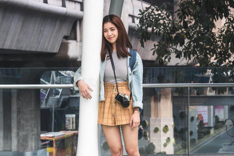 Stående av den unga asiatiska kvinnaturisten som utomhus lutar mot en pol i stads- Lopp- och semesterbegrepp royaltyfria foton