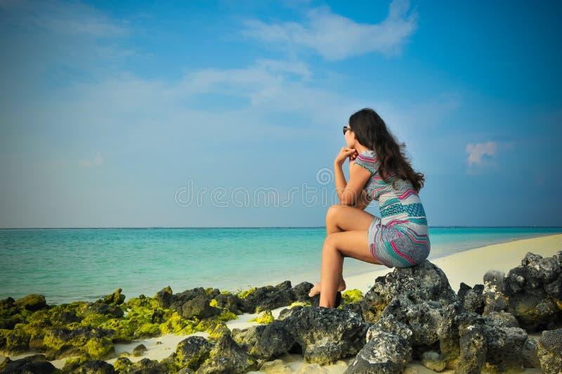 Stående av den unga asiatiska seende kvinnan som tänker på den tropiska stranden på Maldiverna royaltyfria foton