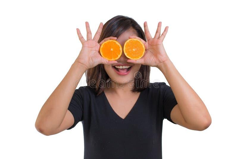 Stående av den unga asiatiska skjortan för svart för kvinnakläder hållande apelsinskivor som är främsta av hennes ögon och leende arkivfoton