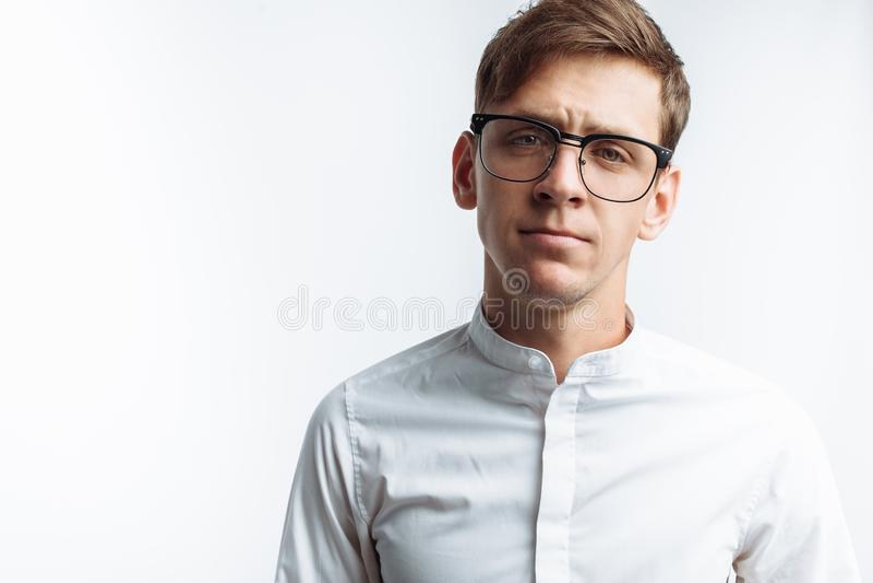 Stående av den unga attraktiva grabben i exponeringsglas, i den vita skjortan som isoleras på vit bakgrund, för annonsering, text fotografering för bildbyråer