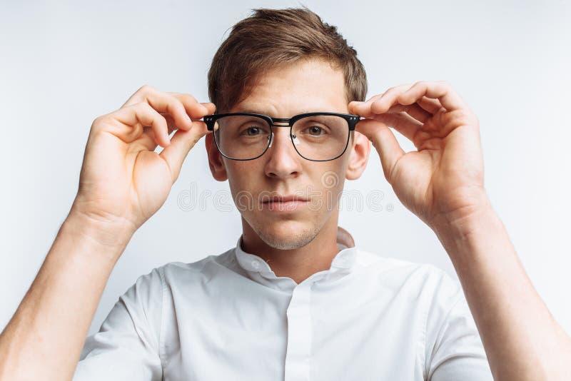 Stående av den unga attraktiva grabben i exponeringsglas, i den vita skjortan som isoleras på vit bakgrund, för annonsering, text arkivfoton