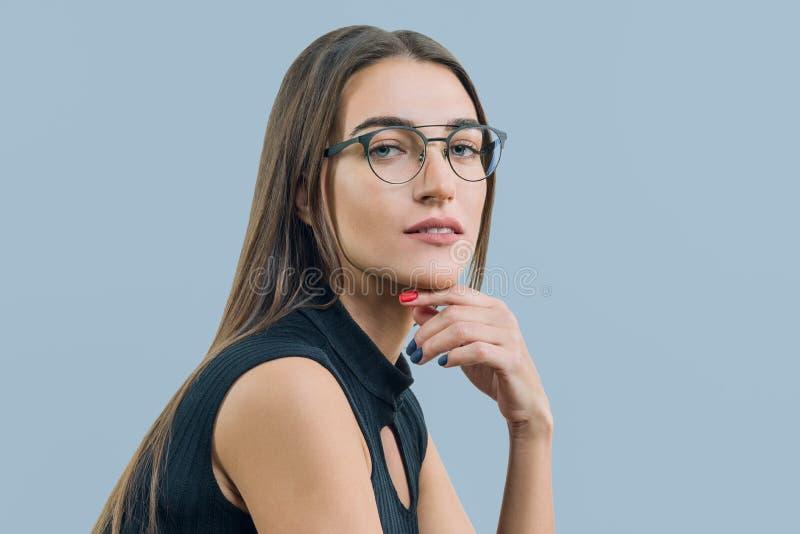 Stående av den unga attraktiva kvinnan med exponeringsglasnärbild, på blå bakgrund, kopieringsutrymme arkivfoton