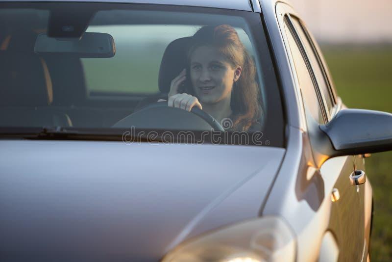 Stående av den unga attraktiva långhåriga le kvinnan inom den skinande silverbilen på styrhjulet som kör och talar på mobil arkivbild